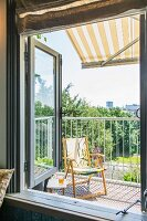 View of yellow folding chair on balcony seen through open window