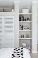 View over bed of shelves in narrow niche and fitted wardrobe with white louvre doors