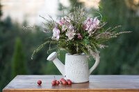 Autumn bouquet of heather, ivy and pink lilies in white ornamental watering can