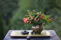 Autumn still-life arrangement with posy of berries in brass vase and plums on tray