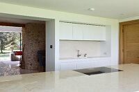 Narrow white fitted kitchen and open doorway leading into living room with stone chimney breast
