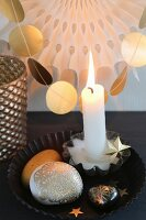 Lit candle and gold-painted pebbles in black cake tin in front of garland of gold paper discs