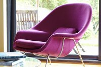 Purple retro shell armchair in front of sliding terrace doors