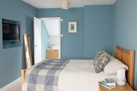 Double bed with wooden headboard in bedroom with blue walls an door leading into bathroom