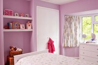 Child's bedroom with pink-painted walls, floating shelves in niche, white fitted wardrobe and chest of drawers below window