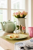 Plate of cake, vase of roses and teapot on table