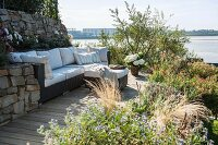 Modern outdoor sofa with pale cushions on sunny terrace with view of the Elbe