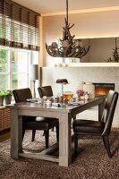 Leather chairs around set table below antler chandelier in corner of dining room