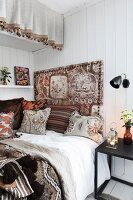Bed decorated with vintage fabrics in a mixture of patterns