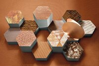 Fabric patterns on honeycomb-shaped objects in shades of nickel, copper and brass