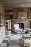 Side tables in rustic living room with simple fireplace in brick surround