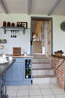 Blue-grey country-house-style cabinets in kitchen with steps leading through doorway into living area