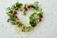Heart-shaped wreath of wild strawberries and elderflowers