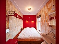 Bed against bright red wall and designer wallpaper on facing walls in narrow bedroom