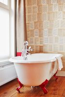 Vintage-style free-standing bathtub with red claw feet against patterned wallpaper