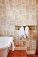 Bathtub next to towel hooks with shelf on wall with patterned wallpaper