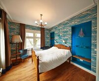 Wood-framed double bed against wall with patterned wallpaper and shelves in blue-painted niches