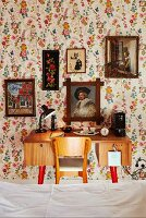 View across bed to 50s-style desk and chair below collection of pictures on floral wallpaper