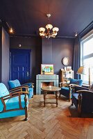 Blue salon with herringbone parquet floor, armchairs in various shades of blue and open fireplace in background