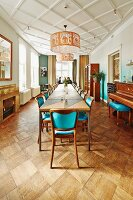 Long table, chairs with turquoise upholstery and pendant lamps suspended from diagonally panelled white ceiling in dining room
