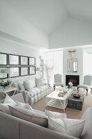 White and grey sofas, modern fireplace and antique-style upholstered chairs