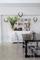 Colonial-style table, postmodern Ghost chairs, pictures and antlers above antique chest of drawers