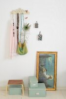 Vintage coat rack, vintage-style religious painting and storage boxes on floor