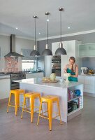 Yellow retro stools at kitchen counter below pendant lamps; woman decorating cake
