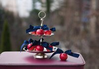 Red apples and dark blue ribbons on silver cake stand