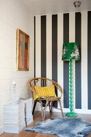 Rattan chair in corner of room against black and white striped wall and next to green retro standard lamp