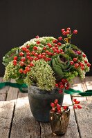 Autumnal flower arrangement with rose hips in vase