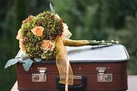 Festive bouquet of apricot roses and hydrangeas tied with ribbon on top of vintage suitcase