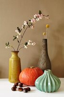 Autumnal still-life arrangement of vases, sprig of flowers, Hokkaido pumpkin and chestnuts