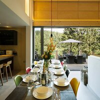 Set table and colourful chairs in open-plan interior; view of furnished terrace in background