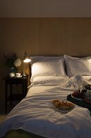 Lit bedside table next to double bed with white bed linen and breakfast tray in foreground