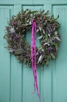 Wreath of lavender and sage hung on turquoise wooden door