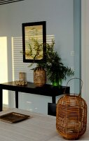 Wicker lantern and black console table against pale blue wall
