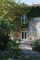 View from garden to gravel terrace outside Mediterranean country house