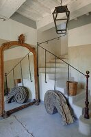 Masonry winding staircase, old full-length mirror and vintage, spiral, architectural wooden element in rustic stairwell