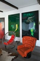Retro orange leather armchair next to transparent shell chair in front of large modern artworks