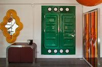Postmodern occasional furniture, orange and red artwork, yellow-framed mirror and green plastic cupboard in pop-art interior