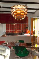 Dining table and coloured transparent plastic shell chairs below Artichoke pendant lamp; kitchen with orange glass tiles in background