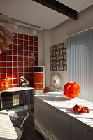 Orange table lamp on white kitchen counter below window and Madonna figurine on retro sideboard against red glass wall tiles