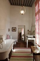 Free-standing vintage bathtub opposite window in rustic bathroom