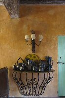 Collection of jugs on vintage console table on ochre wall