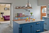 Kitchen island with blue base units and marble and walnut worksurfaces