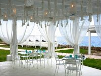 Set table on white wooden terrace with curtains and sea view