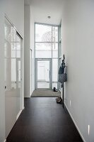 High-ceilinged narrow hallway with black-tiled floor, fitted cupboards with white sliding doors to one side and glazed house entrance at far end