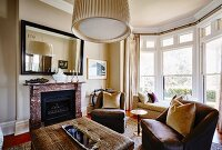 Traditional living room with bay window, comfortable brown easy chairs and fireplace with marble surround