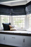 Cushioned window seat with cupboards below, lead glazed bay window and dark grey Roman blinds